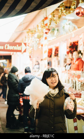 STRASBOURG, FRANCE - DEC 23, 2017: Happy chinese young woman holding a big Cotton candy walking between the rows of Christmas market in Strasbourg Alsace - Stock Photo