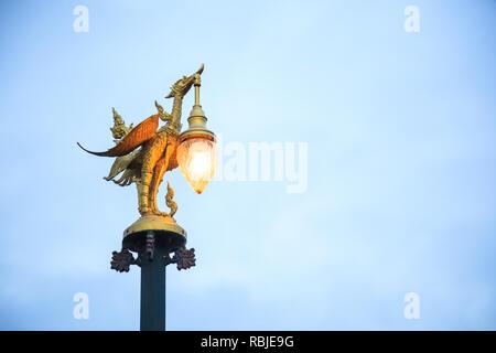 Kanchanaburi, Thailand - December 30, 2018: Golden Swan Sculptural Street Lamp in Thai Contemporary Art glows in twilight on Mon Bridge in Sangkhlabur - Stock Photo