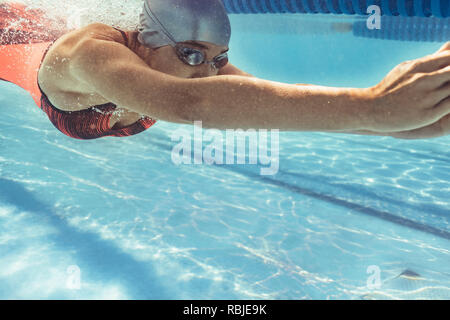 Underwater shot of female swimmer swimming in pool. Young woman swimming in a sport pool. - Stock Photo
