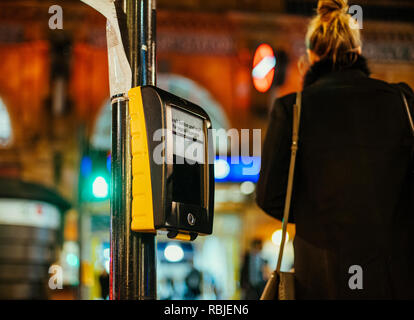 Woman silhouette and push button and wait for siganl opposite sign on the rossing ligt street semaphore traffic light in central london, United Kingdom with defocused city in the background - Stock Photo