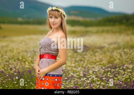 Beautiful woman enjoying daisy field, nice female lying down in meadow of flowers, pretty girl relaxing outdoor, having fun, holding plant, happy youn - Stock Photo