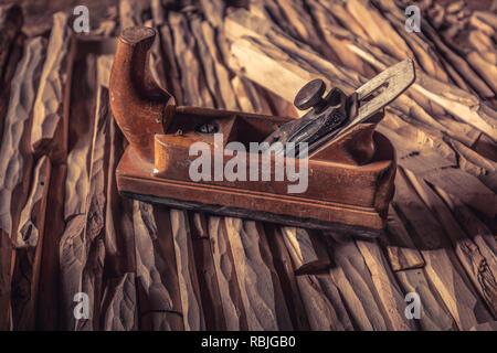 vintage  hand planer on carved wood - Stock Photo