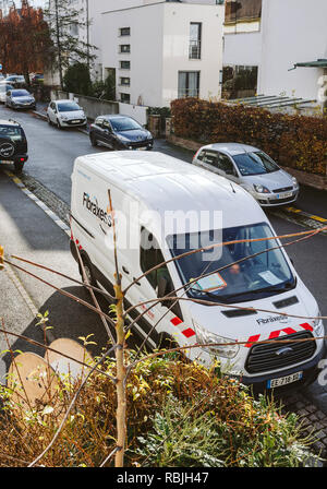 PARIS, FRANCE - NOV 30, 2017: White Ford van from Fibraxess fiber optic installation company parked in residential area for internet connection installation - Stock Photo