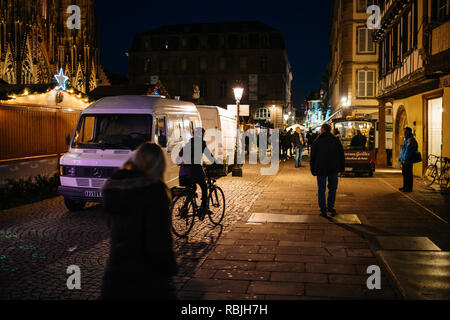 STRASBOURG, FRANCE - NOV 21, 2017: Pedestrians and cyclist near the Christmas stalls walking at night a before the official inauguration of christmas market - Stock Photo
