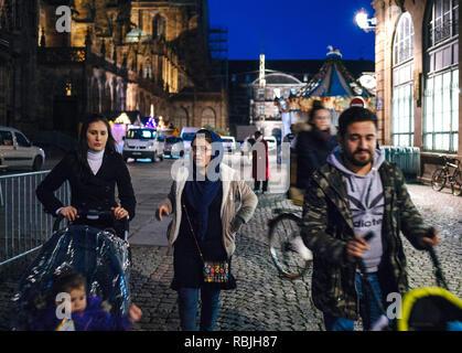 STRASBOURG, FRANCE - NOV 21, 2017: Young muslim family walking at night a day before the official inauguration of Strasbourg Christmas Market - Stock Photo