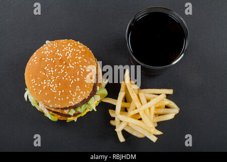 Top view of fresh cheeseburger with beef, cheddar and lettuce in a sesame bun, french fries and a glass of Coca-Cola on black background - Stock Photo
