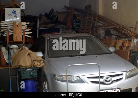 hoarders garage, car surrounded by random wood and other objects - Stock Photo