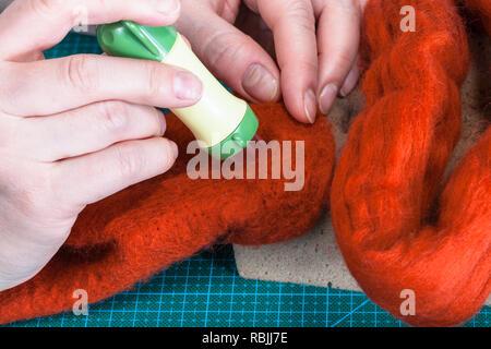 master class of repairing fleece glove using Needle felting process - craftsman poking felt with felting punch close up - Stock Photo