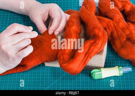 master class of repairing fleece glove using Needle felting process - craftsman binding fibers in felt with felting needle - Stock Photo