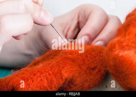 master class of repairing fleece glove using Needle felting process - craftsman binds felted cloth with felting needle close up - Stock Photo