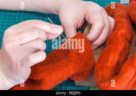 master class of repairing fleece glove using Needle felting process - craftsman repairs felted glove with felting needle - Stock Photo