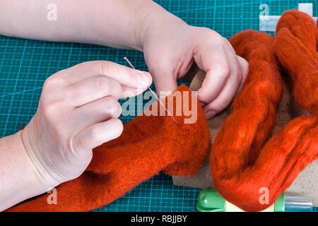 master class of repairing fleece glove using Needle felting process - craftsman fixes fibers in felt with felting needle - Stock Photo