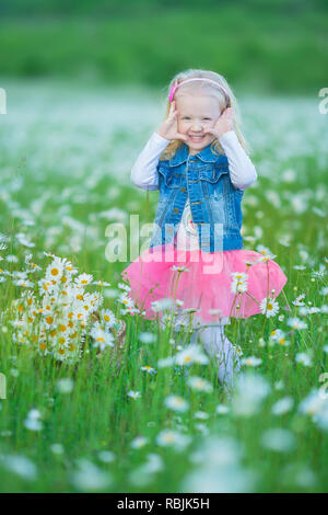 Cute little smiling baby girl in chamomile field Little blond child with wreath on head in chamomiles wearing jeans and pink skirt enjoying hide-and-s - Stock Photo