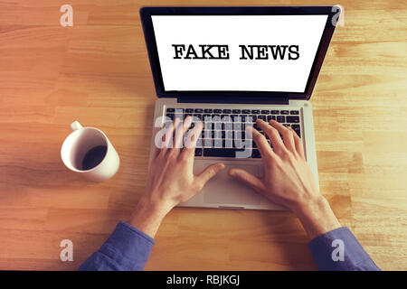 Fake news. Business man hands on laptop keyboard - Stock Photo