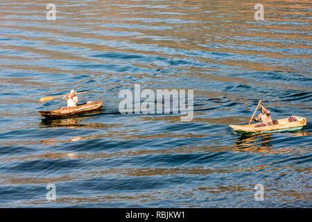 Panajachel, Lake Atitlan, Guatemala - December 23, 2018: Fishermen paddle in traditional wooden boats in early morning on Lake Atitlan - Stock Photo
