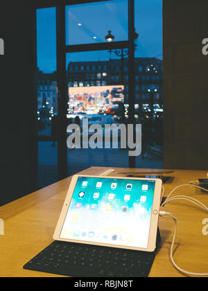 STRASBOURG, FRANCE - JAN 10, 2018: Vertical image of Apple iPad Pro laptop computer in Apple Store with dusk city scenery seen through window - Stock Photo