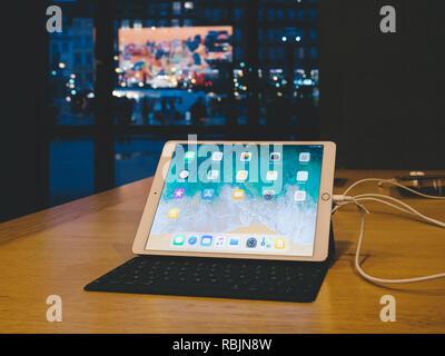STRASBOURG, FRANCE - JAN 10, 2018: Apple iPad Pro laptop computer in Apple Store with dusk city scenery seen through window - Stock Photo