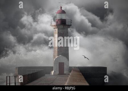 Old lighthouse against an enhanced cloudy stormy sky - Stock Photo