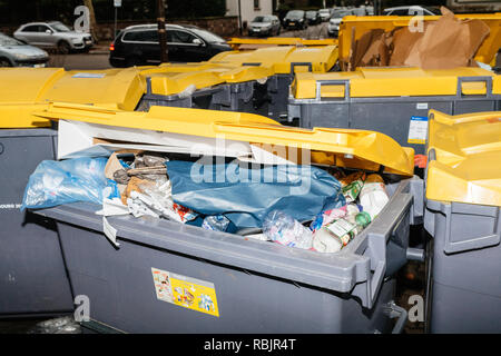 Paris, France - Jan 1, 2019: French street in Paris with dumpsters full with paper cardboard boxes after new year holidays - Stock Photo