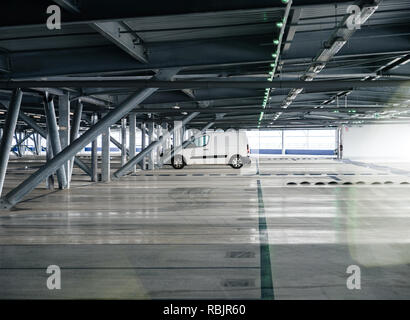 Small white van parked in modern airport parking - Stock Photo