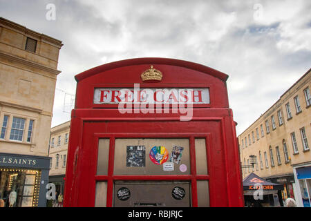 Old red telephone box now used as a cash machine in Bath, England, UK - Stock Photo