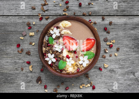 bowl of choclate and banana smoothie with chocolate granola, strawberry and pomegranate seeds decorated with flowers. top view. healthy breakfast - Stock Photo