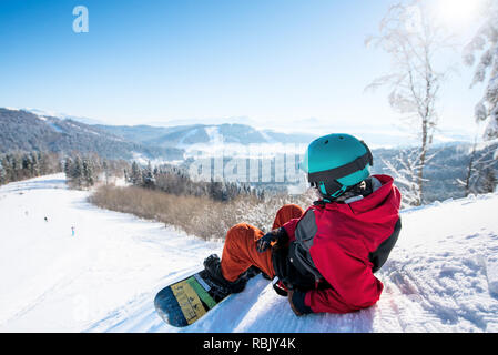 Rearview shot of a relaxed man snowboarder lying on the snowy slope enjoying stunning mountains view resting after riding at the winter resort copyspace landscape recreational lifestyle activity - Stock Photo