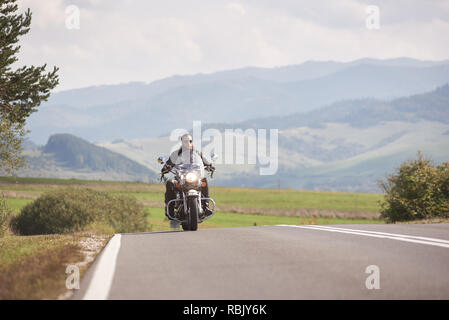 Motorcyclist in black leather outfit riding cruiser bike along road on bright sunny summer day on background foggy distant green woody hills under blue morning sky. - Stock Photo