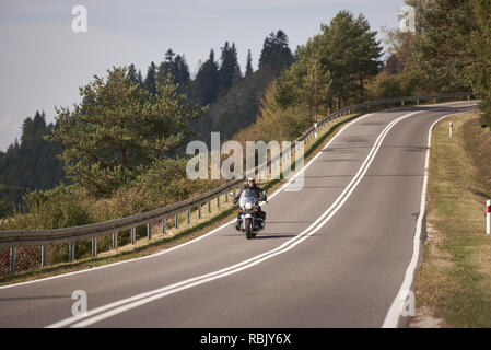 Motorcyclist in black leather outfit riding cruiser motorcycle along twisted road on bright sunny summer day on background of foggy distant green woody hills under blue morning sky. - Stock Photo