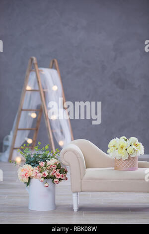 Interior mock up photo. Blue wall with leather material divan sofa and pot with plant flowers and ladder. Background photo with copy space for text - Stock Photo