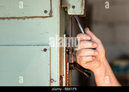 A male worker operating an industrial toggle switch. - Stock Photo