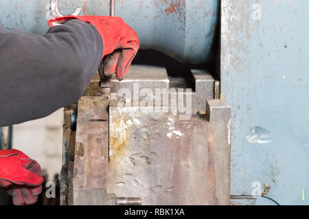 Detail of an male operator securing a profile die inside an aluminium extrusion press. - Stock Photo