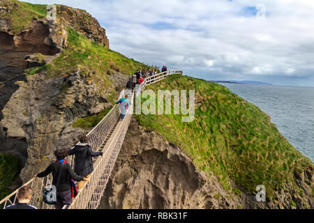 Tourists and visitors explore and walk across the Rope Bridge at Carrick-A-Rede and Larrybane Bay on the West Coast of Ireland. - Stock Photo