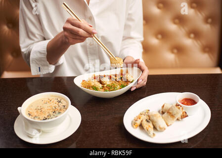 Lady in white blouse sitting in luxury restaurant and eating tasty meal. Three courses lunch from soup, noodles and tempura shrimps on special offer. Girl tasting oriental style dish. - Stock Photo