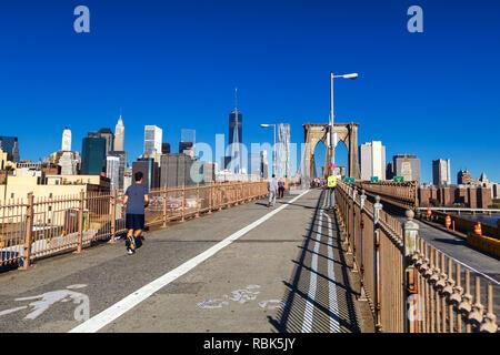 People running and walking on Brooklyn bridge with Manhattan skyline view - Stock Photo