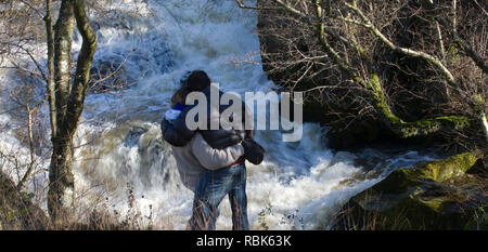 Rear view of couple watching leaping salmon. River Marteg SSSI, Gilfach farm nature reserve, Radnorshire Wildlife Trust, November. - Stock Photo