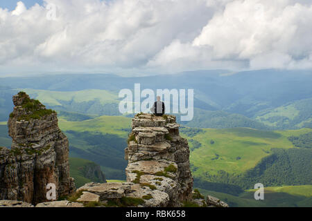 A man sits on the edge of a cliff and looks at the mountains and stormy sky. Plateau Bermamyt. Russia. - Stock Photo