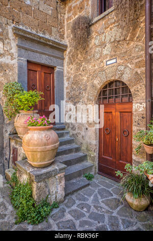 Photograph taken of a romantic, private courtyard of Tuscany. Flowers are flowing from clay vases with weatered wood medieval doors. - Stock Photo
