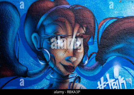 Cartoon like woman's face spray painted on a wall. - Stock Photo