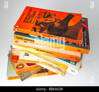 Collection of Penguin paper back books gathering dust from being left on a book shelf  for 20 years . - Stock Photo
