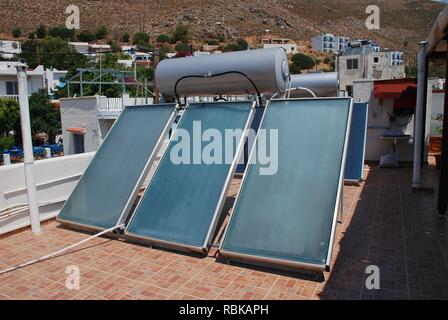 A bank of solar heating panels on a roof top in Livadia on the Greek island of Tilos on June 21, 2018. - Stock Photo