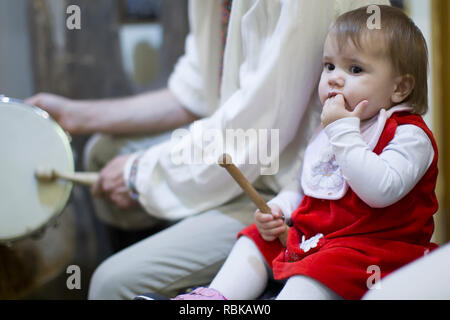 Belarus, Gomel, November 24, 2018. Reconstruction of an ethnic old Belarusian wedding.Baby with drum stick - Stock Photo
