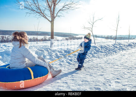 Mom with her little son 3 years old, riding Tubing on a sunny day in city in winter. Play Snorkeling. Happy Scrabing rest in nature. Happy family in the fresh air. - Stock Photo
