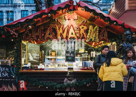London, UK - November 21, 2018: People by the food stand inside Christmas pop up market in Leicester Square. Leicester Square is a famous tourist area - Stock Photo