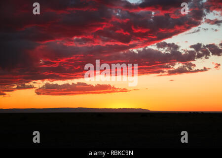 Dramatic sunset / dawn in Gobi Desert with stunning clouds and red sky (Gobi Desert, Mongolia, Asia) - Stock Photo
