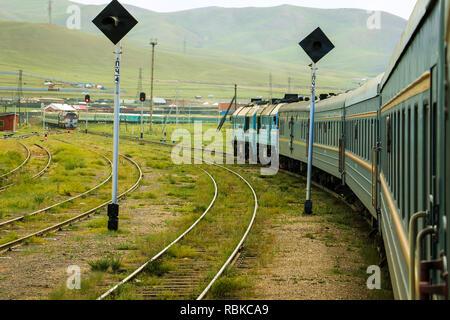 Transsiberian Railway taking a turn in rural Mongolia with another oncoming train near Ulanbaatar (Ulaanbaatar, Mongolia, Asia) - Stock Photo