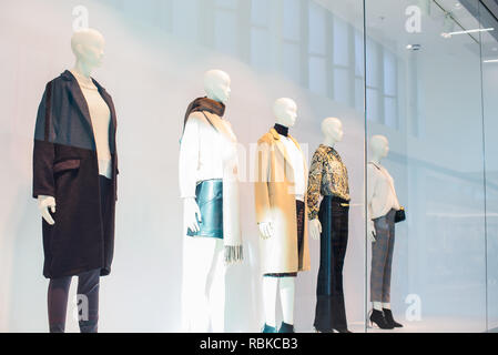 Mannequins in fashion shop display window inside of mall. Female casual style. Side view. Selective focus. Copy space - Stock Photo