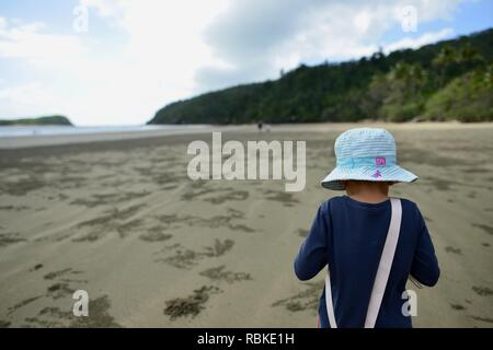 Young child walks alone along a wide open beach in the morning, Hiking through Cape Hillsborough National Park, Queensland, Australia - Stock Photo