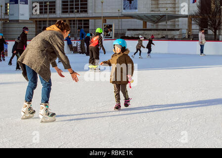 Slovakia, December 2018 ice skating. Mom and child skate on skating shoes.Happy family outdoor ice skating at rink. - Stock Photo