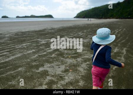 Young child running alone along a wide open beach in the morning, Hiking through Cape Hillsborough National Park, Queensland, Australia - Stock Photo